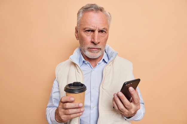 Man bladert draadloos internet op moderne smartphone drinkt cafeïne aromatische drank elegant gekleed ziet er met strikte uitdrukking uit