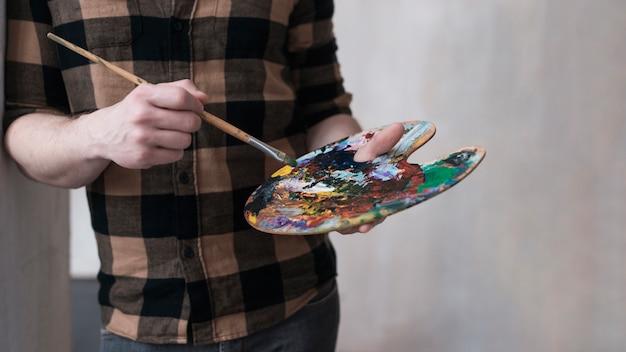 Man blending kleuren voor zijn schilderij