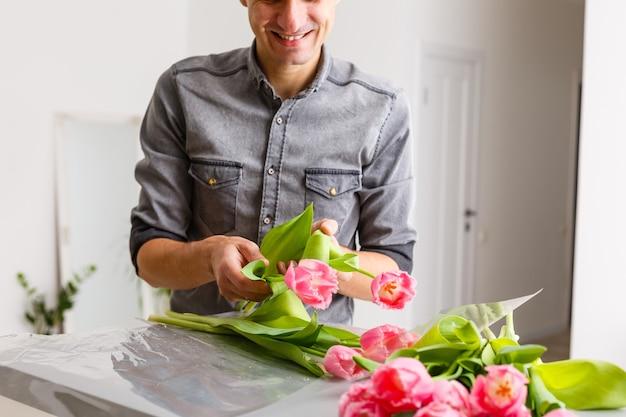 Man bloemist maakt rode tulpenboeket en verpakt in verpakking op houten tafel. bloemen