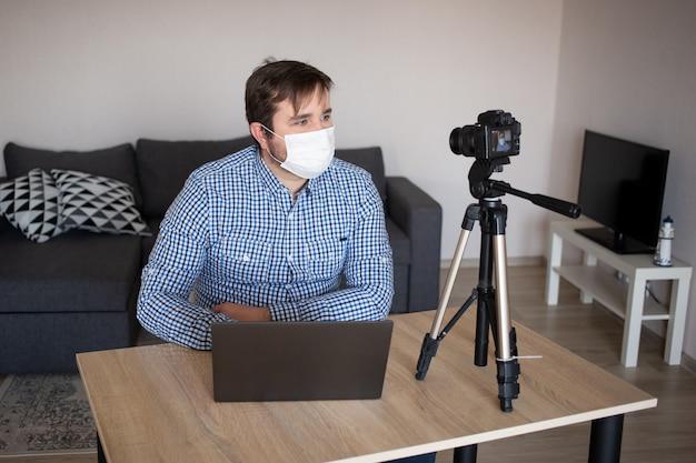 Man blogger met beschermend gezichtsmasker neemt video op videocamera op. mannelijke blogger die over de pandemie van het coronavirus streamt. blijf thuis voor zelfquarantaine op afstand