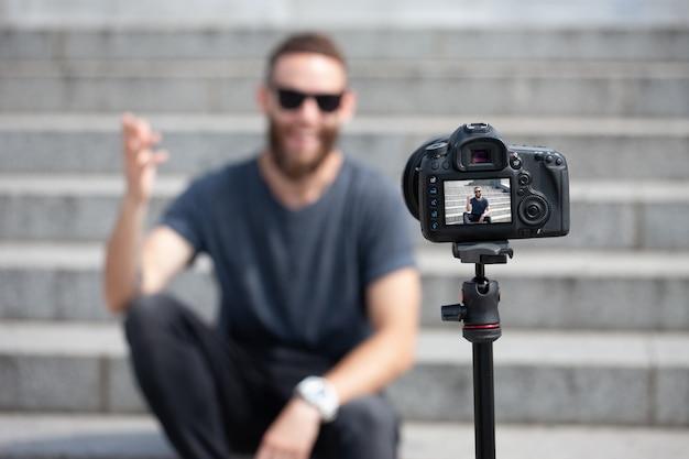Man blogger praten op camera buiten en glimlachen