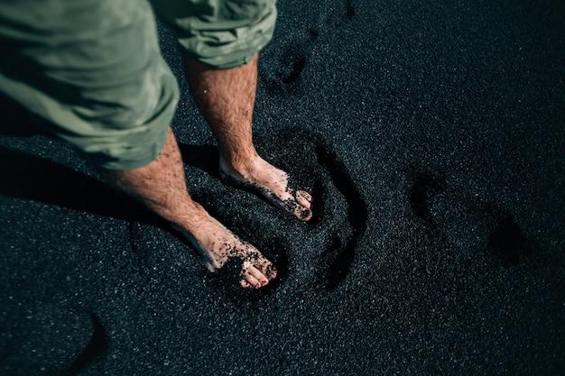 Man blootsvoets op zwart zandstrand in ijsland