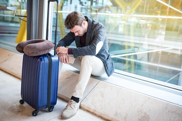 Man boos, verdrietig en boos op de luchthaven zijn vlucht is vertraagd