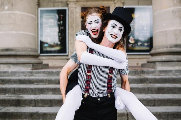 Man bootst het geven van piggyback rit aan vrouwelijke mime