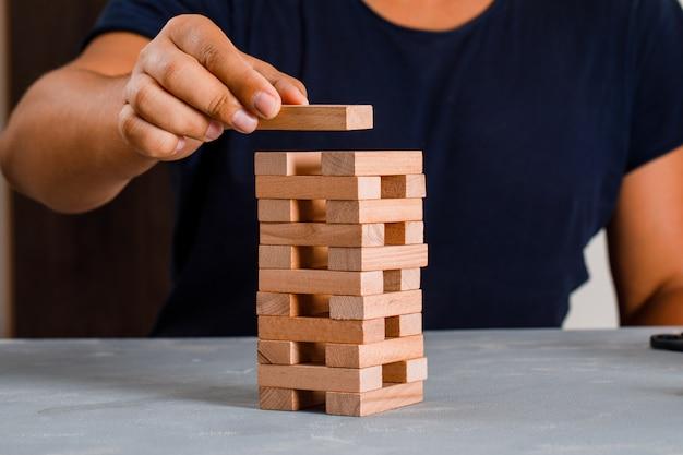 Man bouwen houten blok toren.