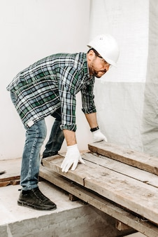 Man bouwer herschikt houten balken op bouwplaats