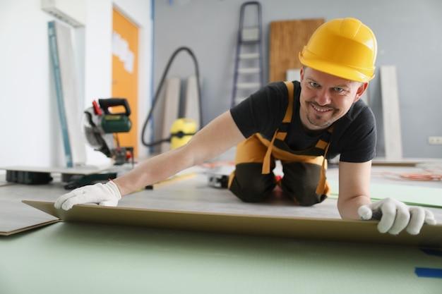 Man bouwer in gele helm liggend laminaat planken op de vloer