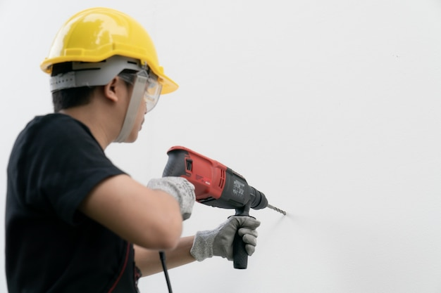 Man bouwer of werknemer met gele helm en bril boormachine op witte muur.