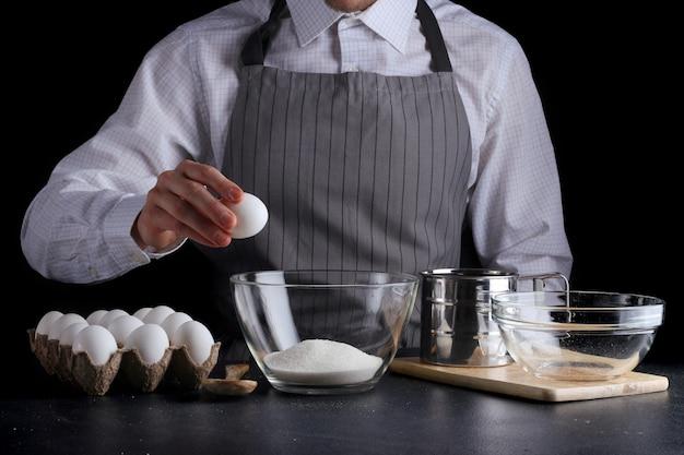 Man breken ei in een kom gebak koken
