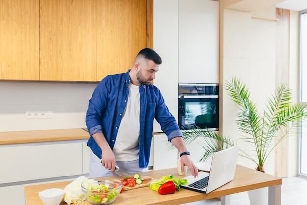 Man brengt een dag thuis door, bereidt een ontbijt met groenten in de keuken een man in huiskleding en met een baard gebruikt een laptop om online koken te leren