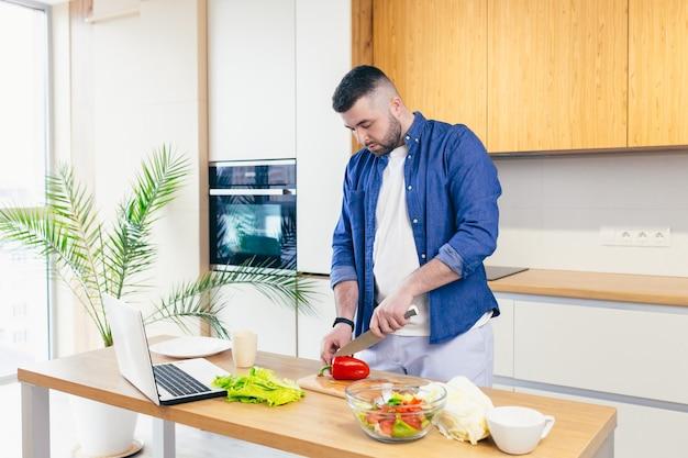 Man brengt een dag thuis door en bereidt een ontbijt met groenten in de keuken