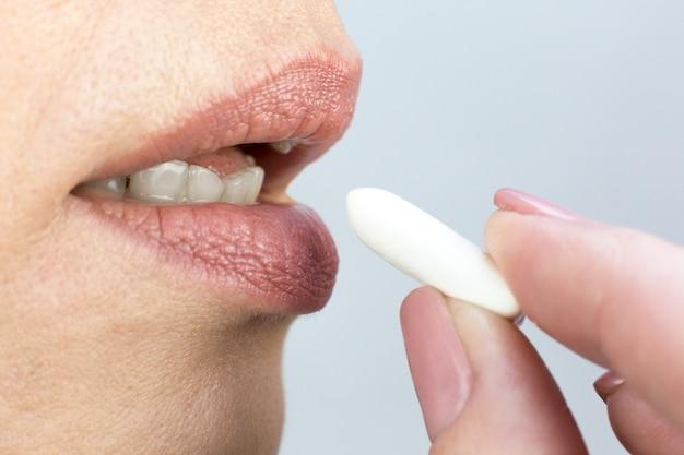 Man brengt kauwgom naar zijn mond, vingers en lippen close-up