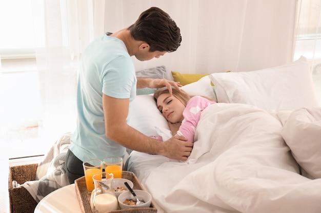 Man brengt ontbijt naar zijn vrouw in bed