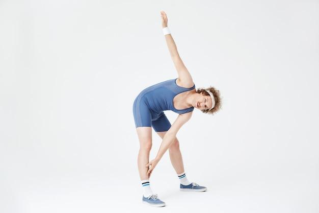 Man buigt in de taille aanraken rechterbeen met linkerhand