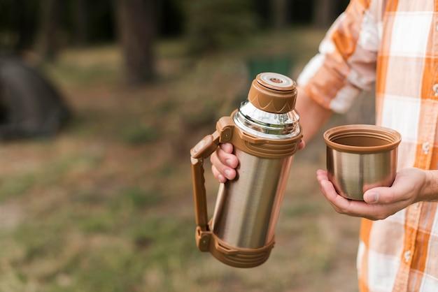 Man buiten kamperen en met een warme drank