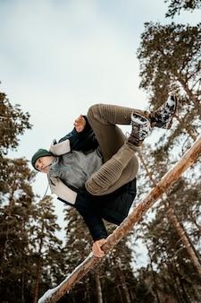Man buiten springen in de winter met sneeuw