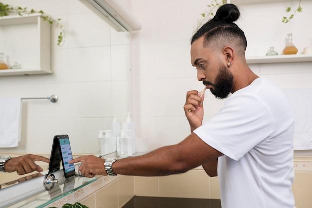 Man checkt zijn telefoon, zelfs in zijn badkamer