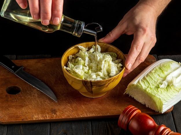 Man chef-kok in uniform olie toe te voegen aan napa koolsalade. het idee om een dieetontbijt of -diner te maken