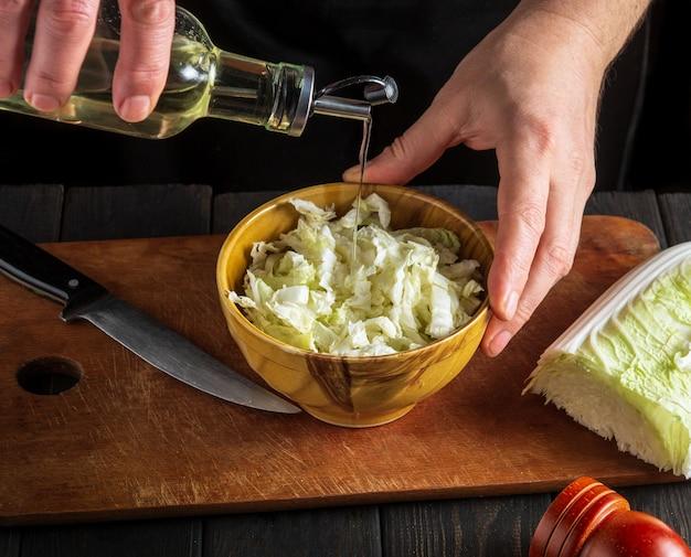 Man chef-kok olie toe te voegen aan napa koolsalade. het idee om een dieetontbijt of -diner te maken