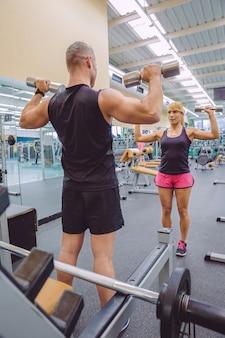 Man coach opleiding tot mooie vrouw met halters oefeningen op fitnesscentrum. persoonlijk trainerconcept.