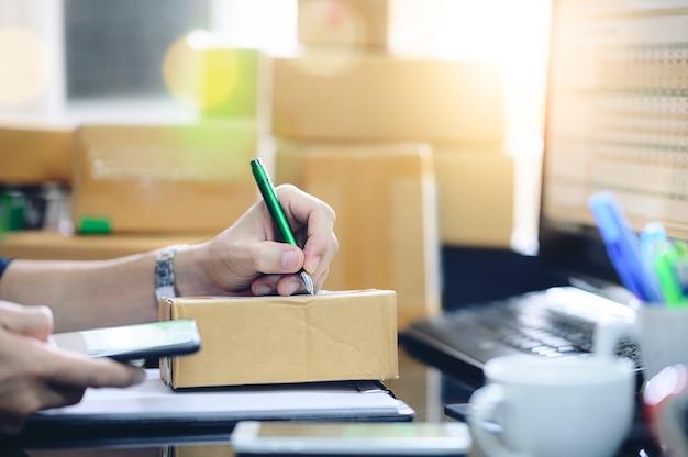 Man controle bestelling in mobiele telefoon en schrijf in de levering op pakket doos.