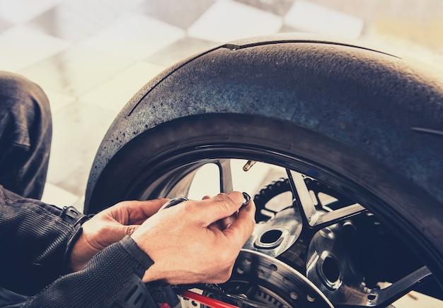 Man controle van de luchtdruk van motorfiets wiel voor op reis