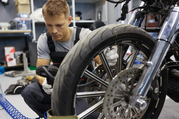 Man controleert bandenspanning op motorfiets in werkplaatsbandenserviceconcept