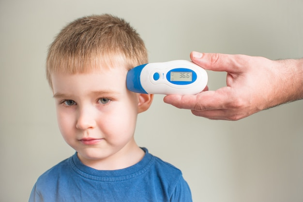 Man controleert de lichaamstemperatuur van de jongen met behulp van een digitale thermometer op het virus covid-19 symptoom - het concept van een epidemie-uitbraak. stop het coronavirus