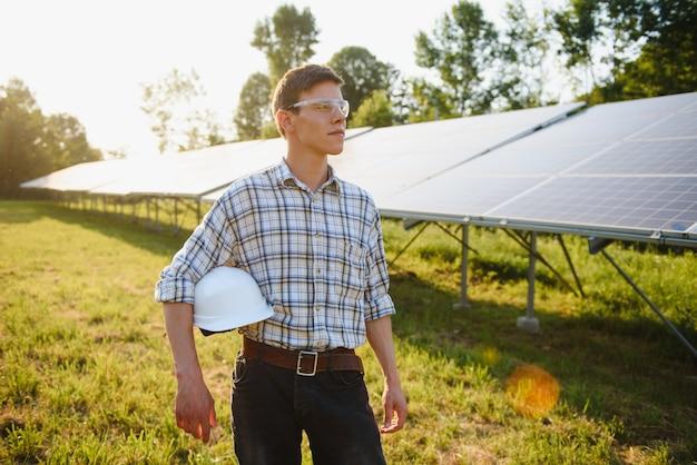Man controleert en staat in de buurt van zonnepanelen