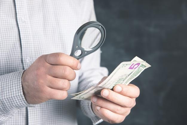 Man controleert geld met een vergrootglas.