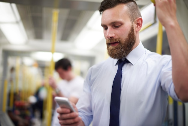 Man controleert nieuws in de mobiele telefoon in de metro