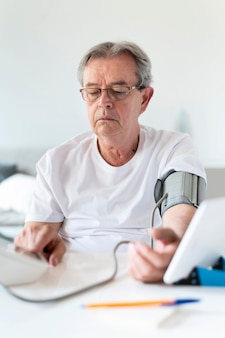 Man controleert verborgen bloeddruk Gratis Foto