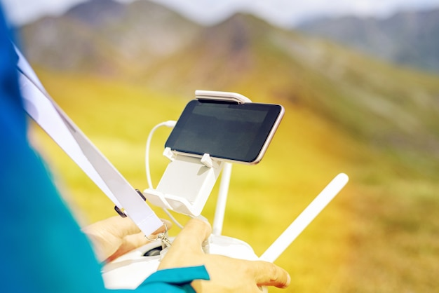 Man controlerende drone met externe en mobiele telefoon