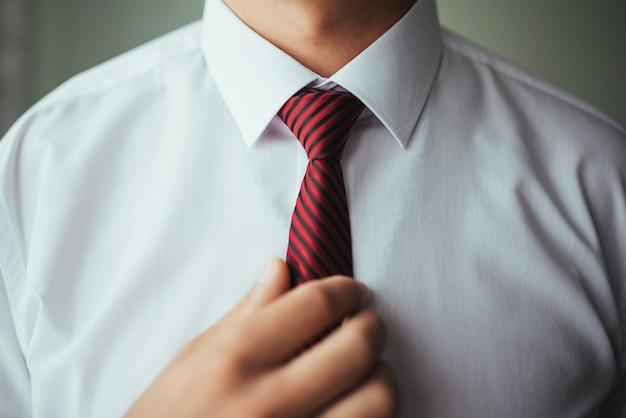 Man corrigeert riem, vergoedingen bruidegom, iemands handen, aankleden, man knoppen broek, jeans