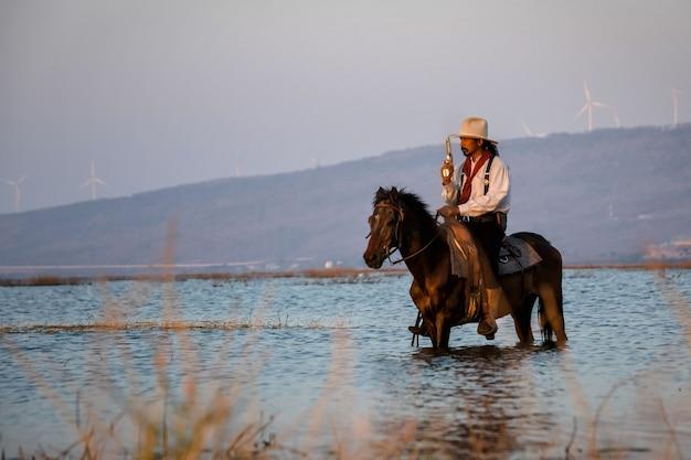 Man cowboy rijdt op een paard, steekt de rivier over