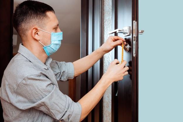 Man de deurknop repareren. close-up van de handen van de werknemer die nieuwe deurkast installeren