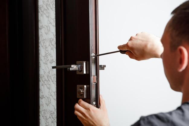 Man de deurknop repareren. timmerman bezig met de installatie van een slot zonder de houten deur van de deurknoppen