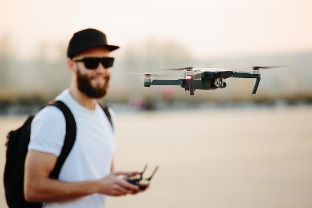 Man de drone bedienen met de afstandsbediening en plezier maken