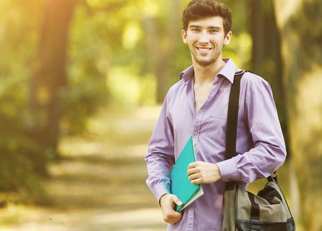 Man de student met boeken in het park