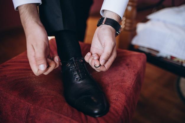 Man de veters op zwarte schoenen op een houten vloer binden