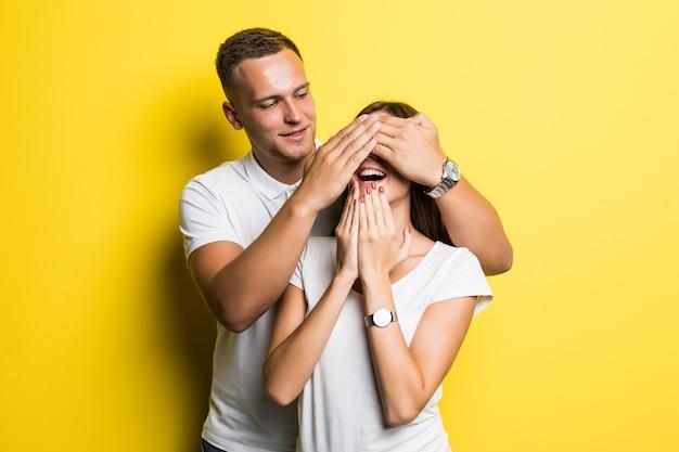 Man dekking ogen zijn vriendin verrassing concept geïsoleerd op geel