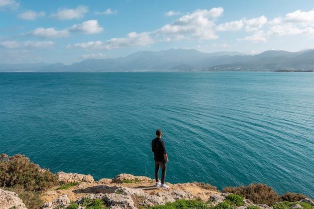 Man die aan de kust staat, kijkend naar de kalme zee.