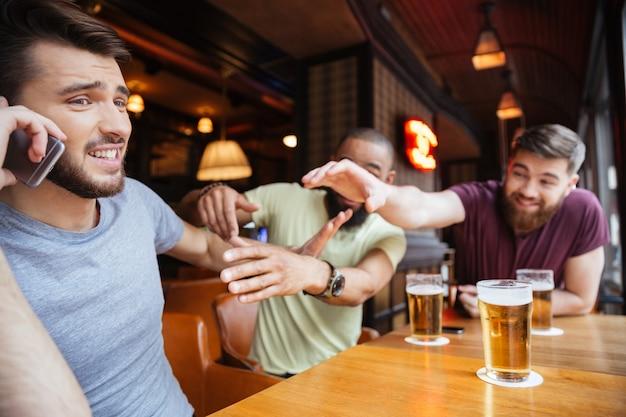 Man die aan de telefoon praat terwijl grappige vrienden hem niet laten doen in een biercafé