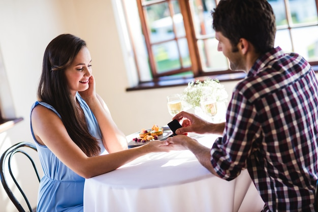 Man die aan vrouw in een restaurant voorstelt