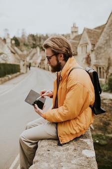 Man die aantekeningen maakt op zijn tablet in het dorp cotswolds, vk
