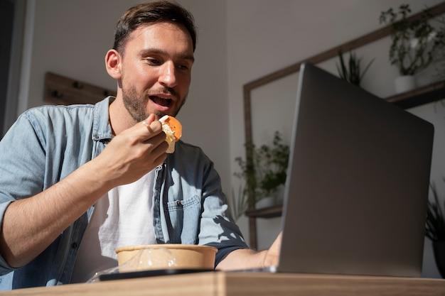 Man die afhaalmaaltijden eet en laptop gebruikt