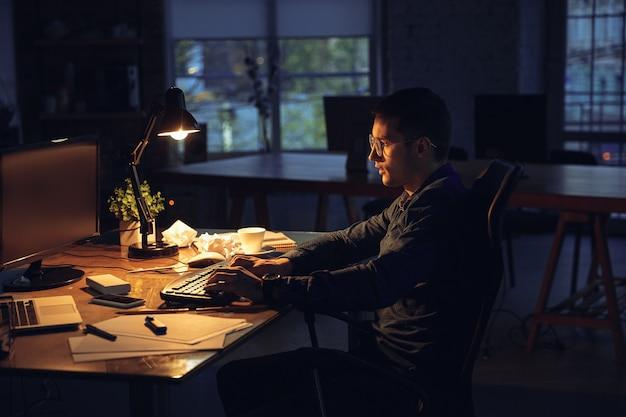 Man die alleen op kantoor werkt tijdens coronavirus of covid-quarantaine die tot laat in de nacht blijft