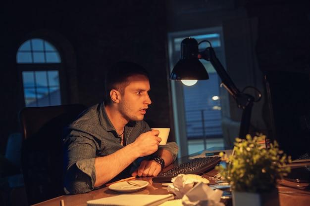 Man die alleen op kantoor werkt tijdens coronavirusquarantaine die tot laat in de nacht blijft