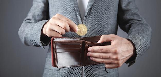Man die bitcoin in zijn portemonnee stopt.