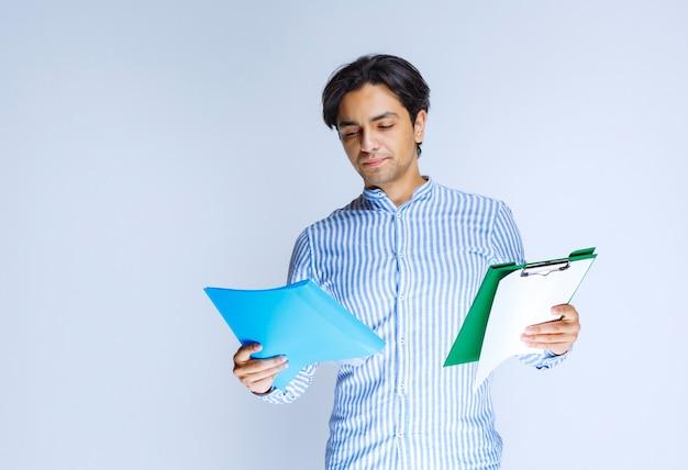 Man die blauwe en groene rapportmappen vasthoudt en ze controleert. hoge kwaliteit foto